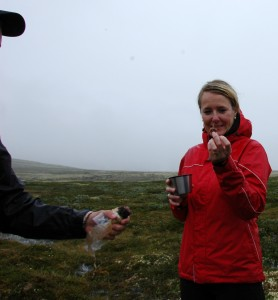 One of the tourists, Heidi, getting her piece of muskox sausage